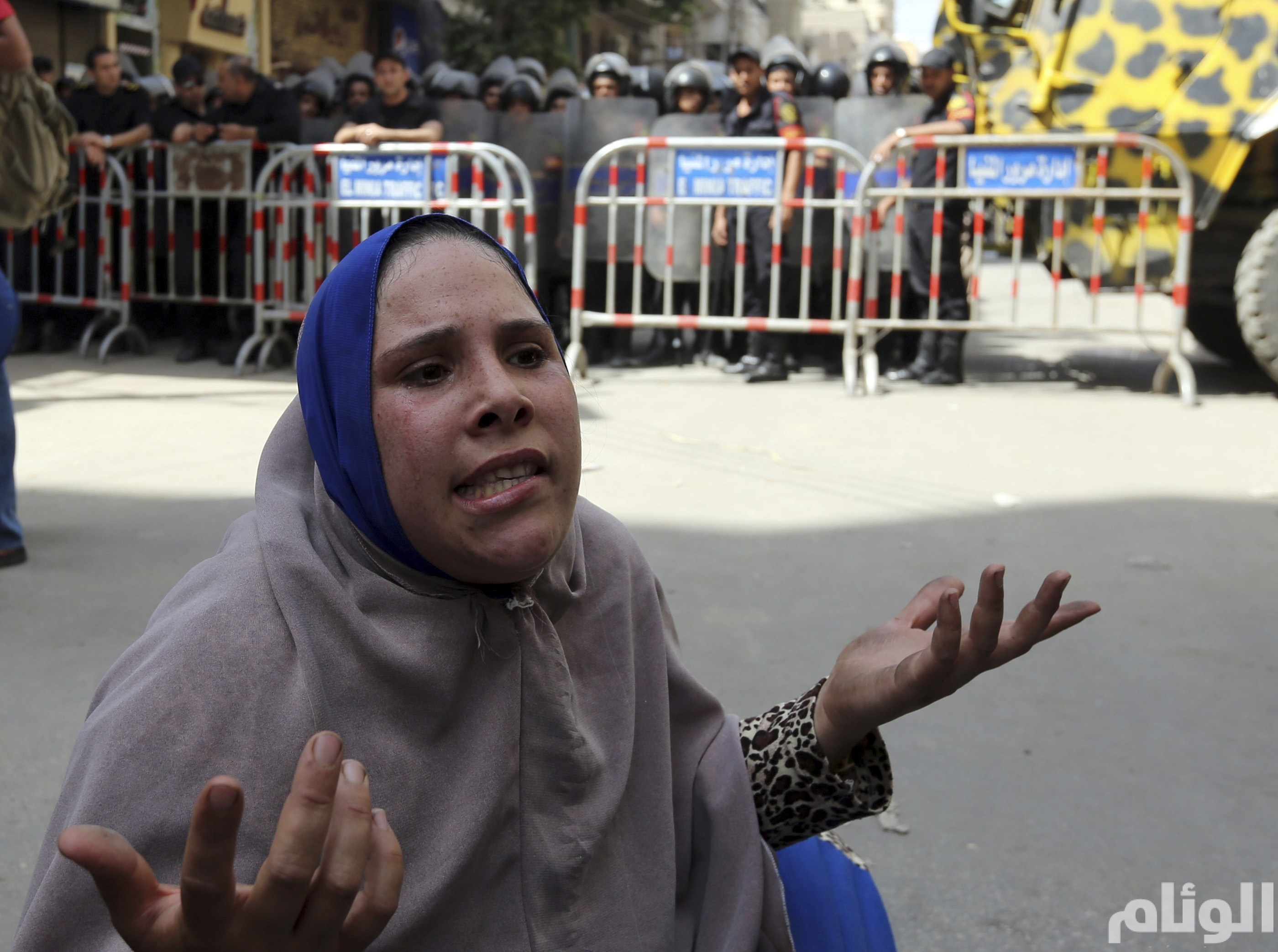 A woman reacts in front of security forces at the court in Minya