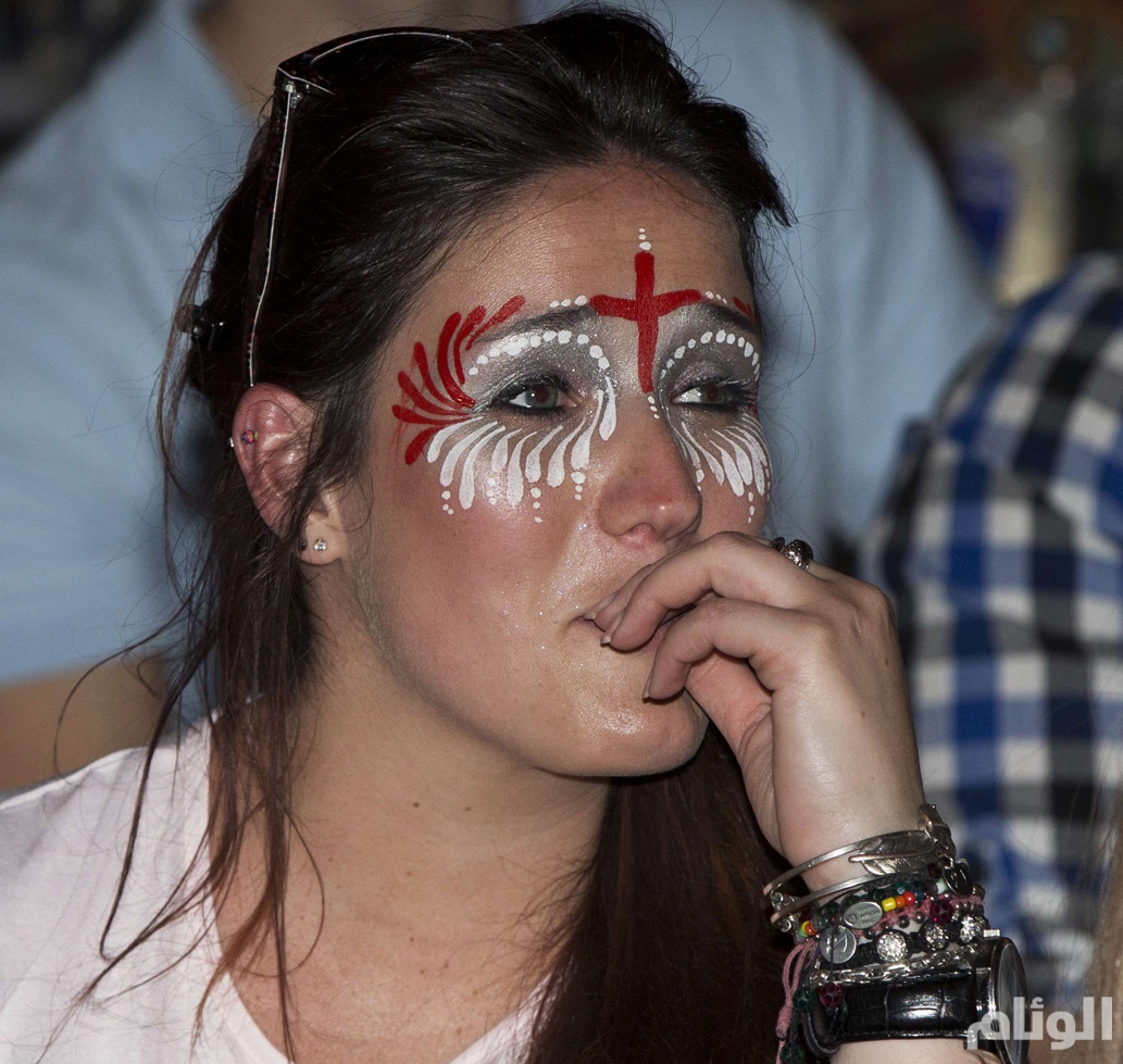 An England soccer fan watches her team play against Italy during the 2014 World Cup at a bar in central London
