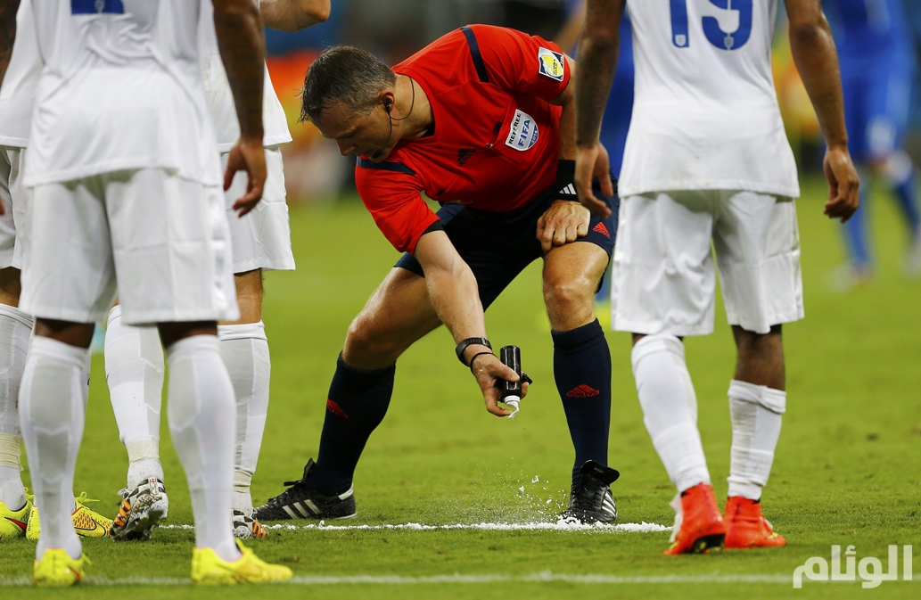 Referee Bjorn Kuipers of the Netherlands marks out a line with a vanishing spray during the 2014 World Cup Group D soccer match between England and Italy at the Amazonia arena in Manaus