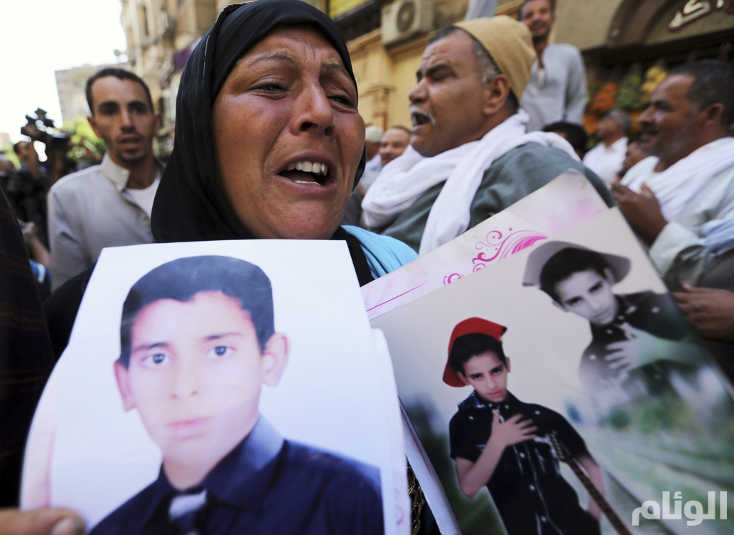 A woman reacts while holding photos of her son outside a court in Minya, south of Cairo