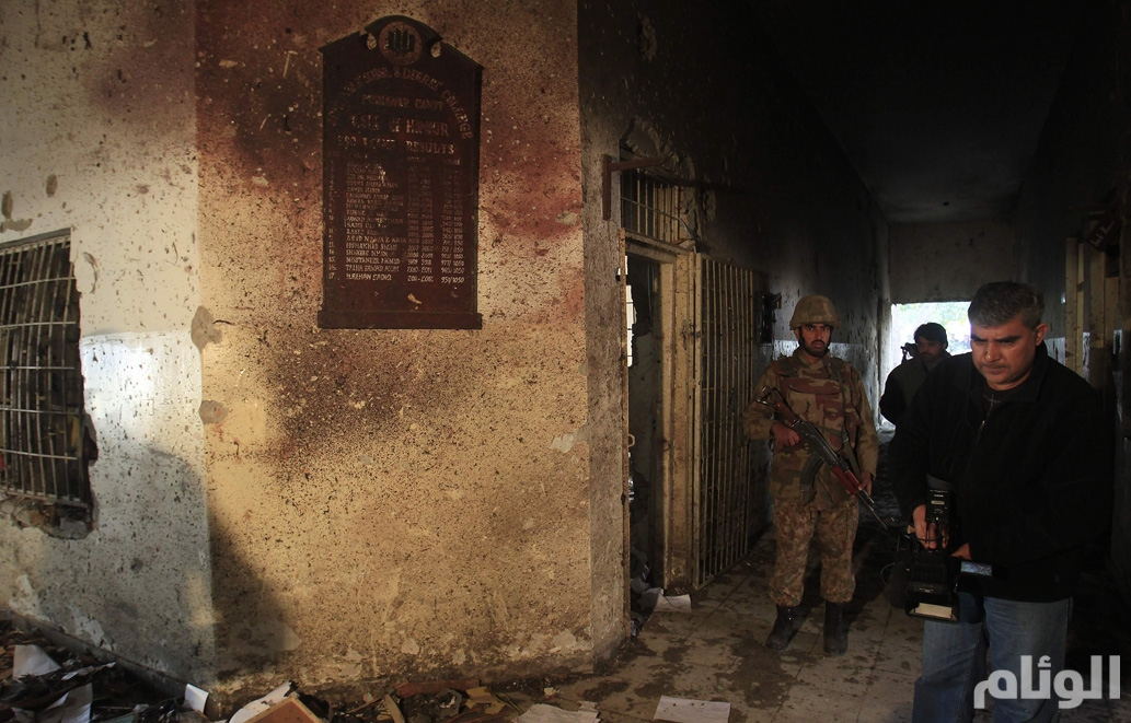 A local cameraman films in front of an army soldier at the Army Public School, which was attacked by Taliban gunmen, in Peshawar