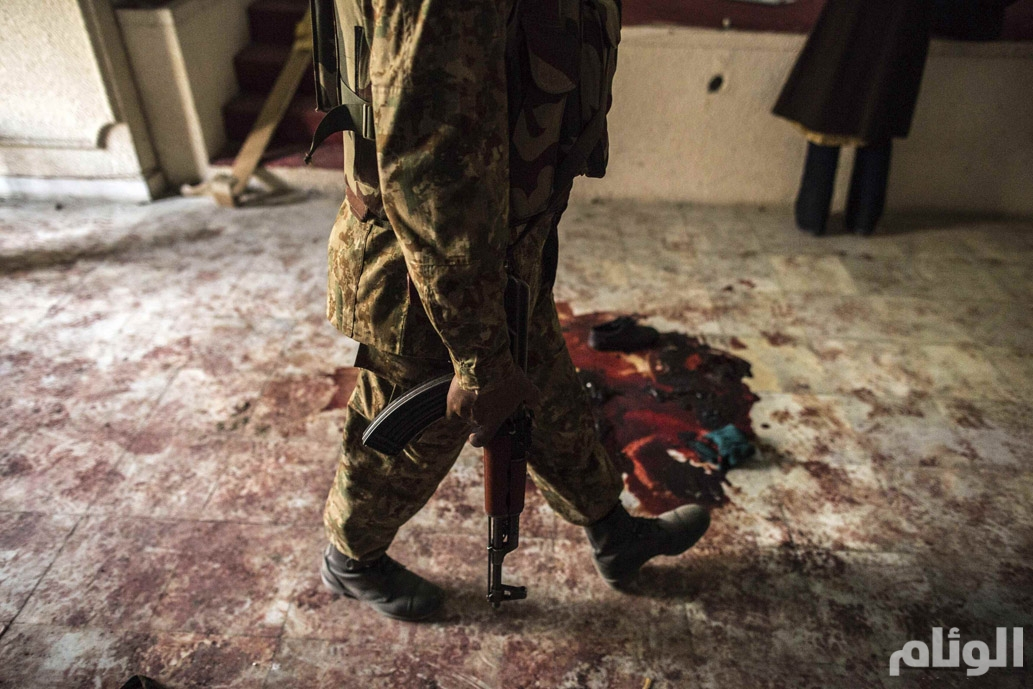 Soldier walks past blood on the auditorium floor at the Army Public School which was attacked by Taliban gunmen, in Peshawar