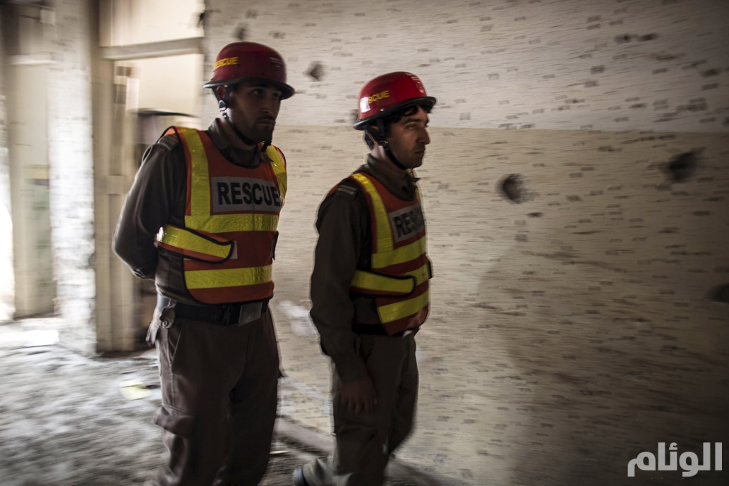 Rescue team members walk inside the Army Public School, which was attacked by Taliban gunmen, in Peshawar