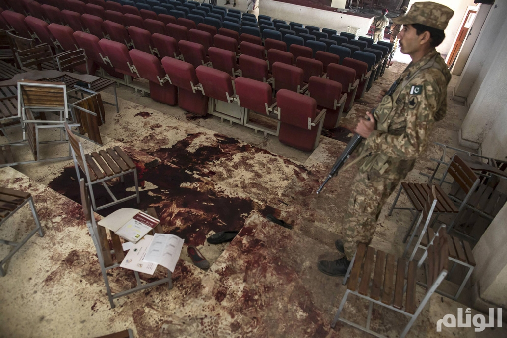 An army soldier stands by blood on the floor at the Army Public School, which was attacked by Taliban gunmen, in Peshawar