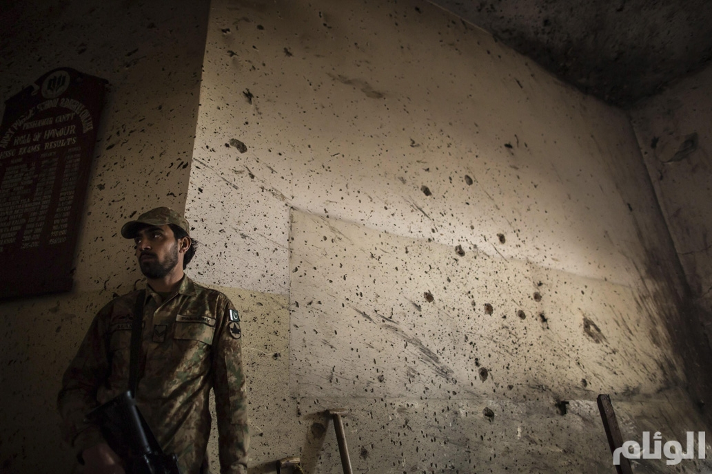 An army soldier stands guard inside the Army Public School, which was attacked by Taliban gunmen, in Peshawar