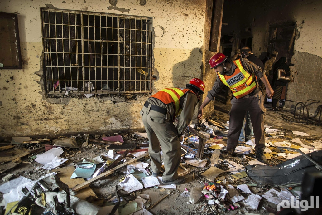Rescue team members go through debris inside the Army Public School, which was attacked by Taliban gunmen, in Peshawar
