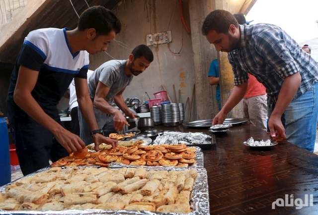 Volunteers prepare food as people wait to eat their Iftar (breaking of fast) meal at tables set up by a charity during the holy fasting month of Ramadan in Benghazi, Libya June 27, 2015. REUTERS/Esam Omran Al-Fetori