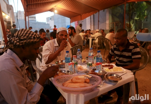People eat their Iftar (breaking of fast) meal at tables offering free food set up by a charity during the holy fasting month of Ramadan in Benghazi, Libya June 27, 2015. REUTERS/Esam Omran Al-Fetori