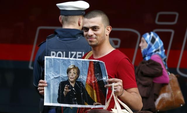 """لاجئ سوري يرفع صورة """"ميركل"""" لحظة وصوله ألمانيا"""