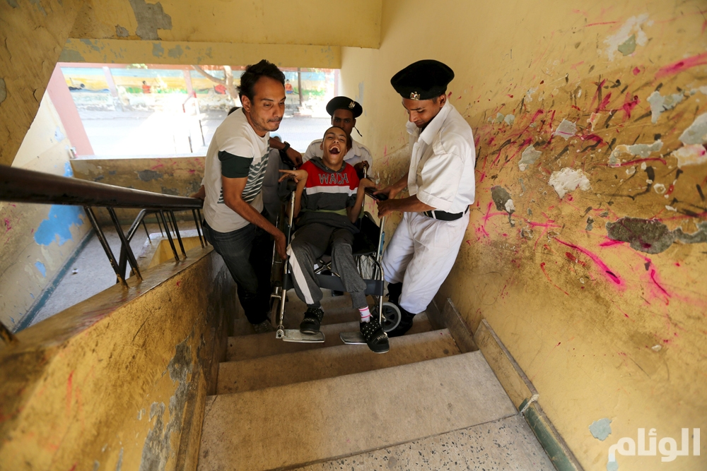 A policeman assists the family of a disabled voter at a school used as a polling station during the run-off to the first round of parliamentary election in Imbaba, Giza governorate, Egypt October 27, 2015. Egyptians voted on Tuesday in run-off elections for more than 200 parliamentary seats in which no clear winner emerged in the first round of polls, with candidates loyal to President Abdel Fattah al-Sisi widely expected to dominate. REUTERS/Mohamed Abd El Ghany