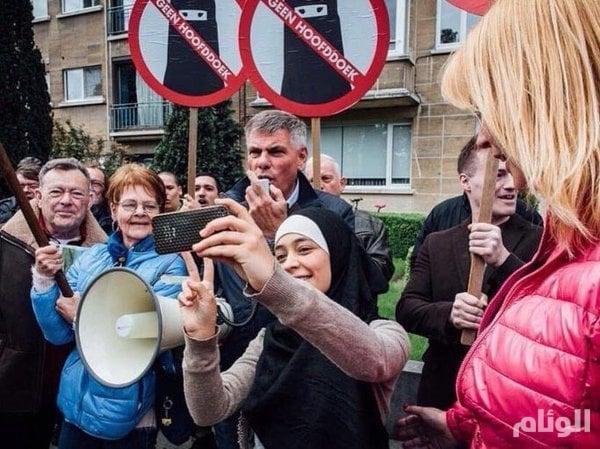 بالصور.. فتاة مسلمة تواجه مظاهرة ضد الإسلام في بلجيكا بصور «سيلفي»
