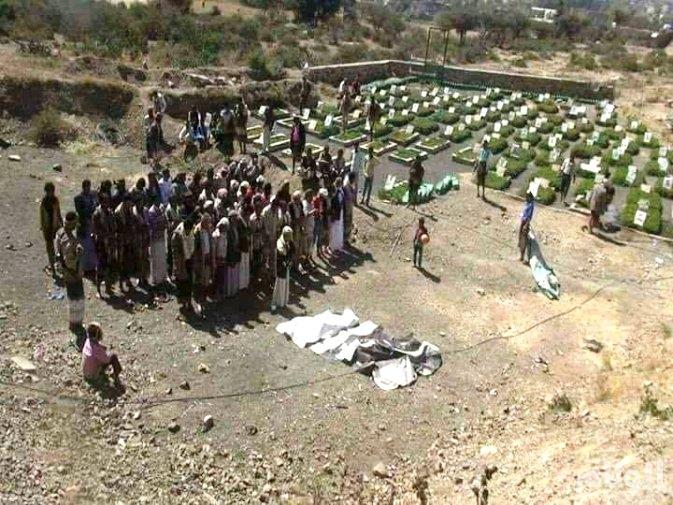 طفل يحمل كرة قدم يتأمل دفن المزيد من قتلى الحوثيين في اليمن