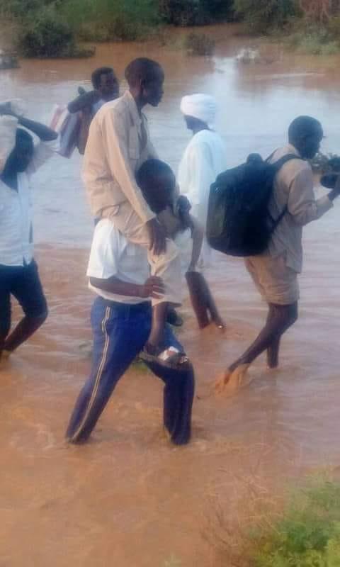 رجل أمن سوداني يحمل مواطناً على كتفه
