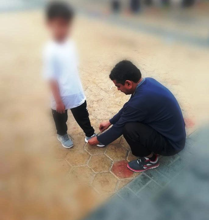 معلم يربط حذاء طالب في فناء المدرسة
