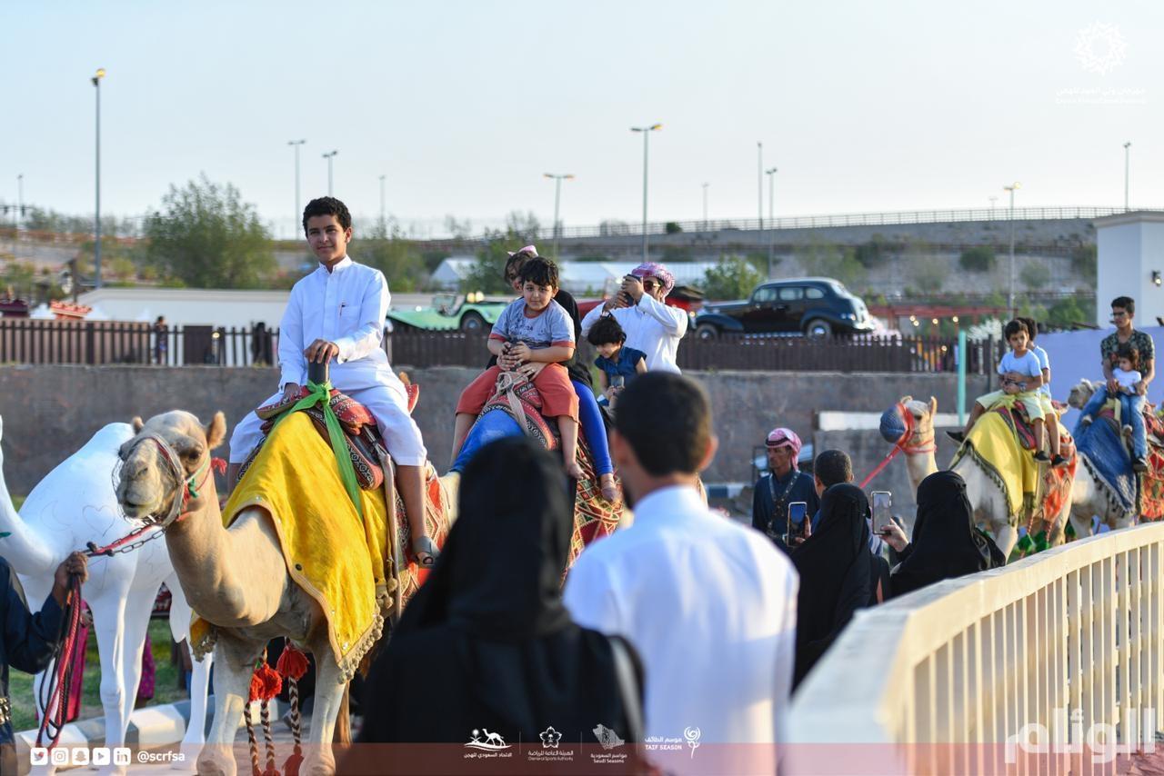 شاهد بالصور ..قافلة قرية الهجن تجول بالعائلات في مهرجان ولي العهد